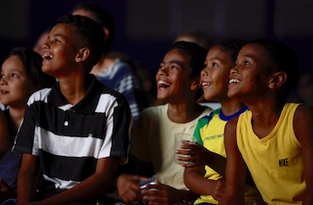 Image of the Turbocharging neighbourhoods project showing Brazilian children laughing as they watch a film